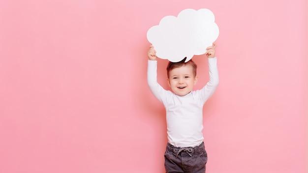 Portret szczęśliwego chłopca z czystą białą tablicą w kształcie chmury