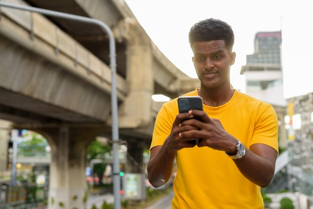 Portret szczęśliwego czarnego afrykańskiego mężczyzny noszącego żółtą koszulkę na zewnątrz w mieście latem podczas korzystania z telefonu komórkowego