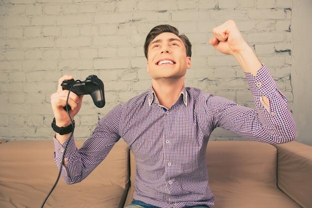Portret szczęśliwego człowieka wygrywającego grę wideo z podniesioną pięścią