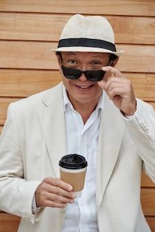 Portret szczęśliwego dojrzałego azjatyckiego mężczyzny w białej kurtce i kapeluszu stra, zdejmującego okulary przeciwsłoneczne i pijącego kawę na zewnątrz