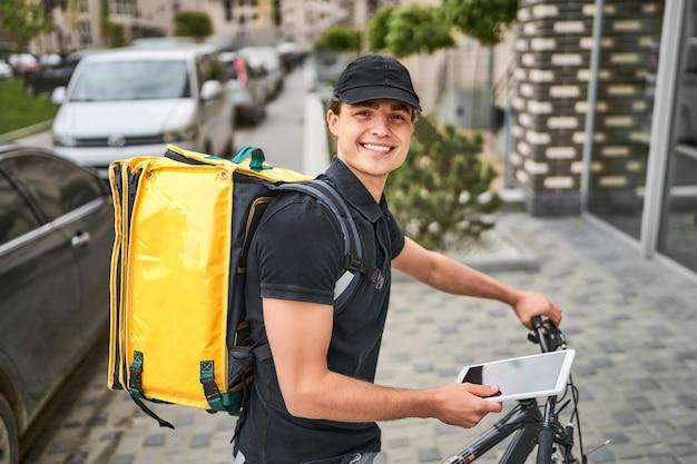 Portret szczęśliwego dostawcy w mundurze na rowerze w pobliżu nowoczesnego domu, z żółtym plecakiem