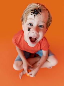 Portret szczęśliwego dzieciaka z twarzą pomalowaną na halloween