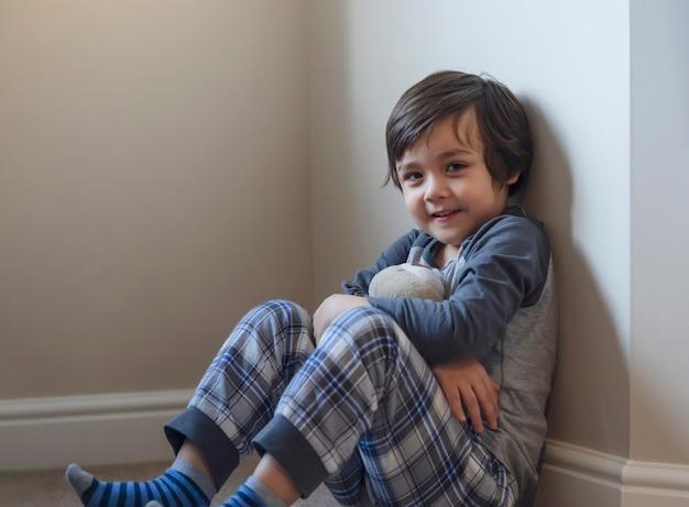 Portret szczęśliwego dzieciaka z uśmiechniętą twarzą relaksującą się w domu, zdrowe dziecko chłopca siedzącego na dywanie, grającego z misiem i patrząc na kamery, dystans społeczny duromg covid blokada w dół