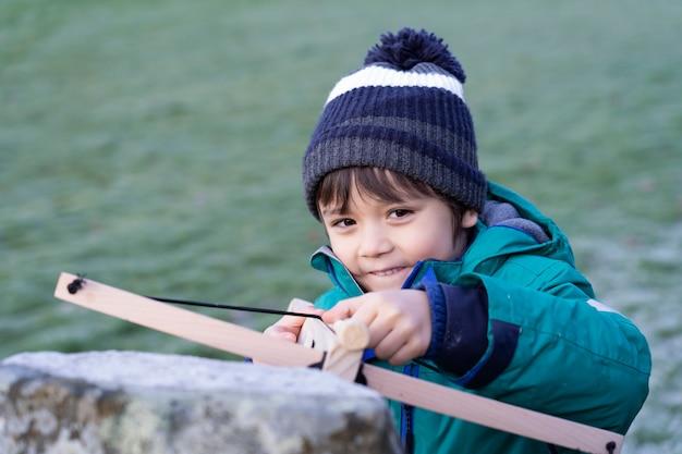 Portret szczęśliwego dzieciaka z uśmiechniętą twarzą stojącą za starą ścianą trzymającą kuszę, aktywne dziecko chowające się za kamienną cegłą strzelać kuszą zabawkę, aktywność na świeżym powietrzu podczas zimnej pogody