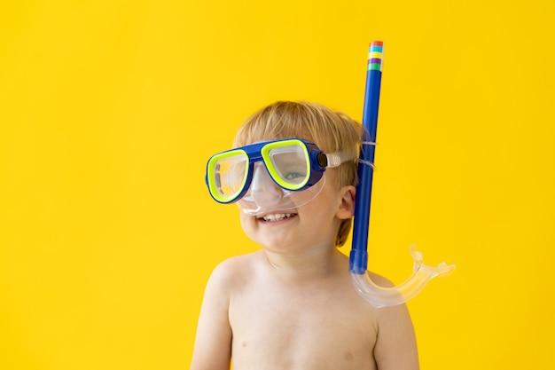 Portret szczęśliwego dziecka przeciw żółtej ścianie na wakacjach.