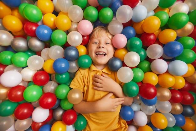 Portret szczęśliwego dziecka, śmiejąc się, leżąc w basenie wśród kolorowych kulek