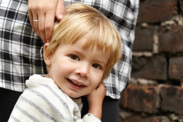 Portret szczęśliwego dziecka spaceru z mamą na ulicy. uśmiechnięty chłopiec z brązowymi oczami, blond włosami. czuje się bezpiecznie, ponieważ matka stoi blisko niego, gotowa do ochrony.