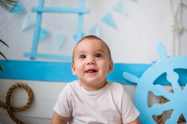 Portret szczęśliwego dziecka w białym body na drewnianej łodzi