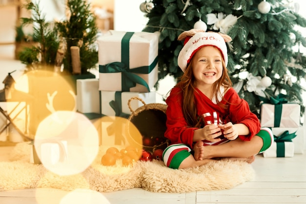 Portret szczęśliwego dziecka w piżamie w kuchni na choince