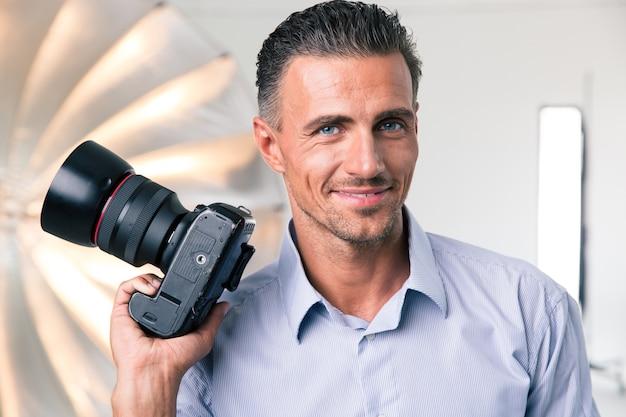 Portret szczęśliwego fotografa trzymającego aparat w studio