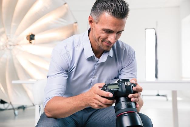 Portret szczęśliwego fotografa używającego aparatu w studio