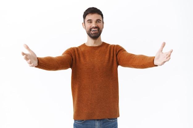 Portret szczęśliwego i przyjaznego brodatego mężczyzny ciepło powita drogiego gościa, rozłóż ręce na boki w przytuleniu lub uścisku, uśmiechnięta osoba witająca z miłością, stojąca biała ściana