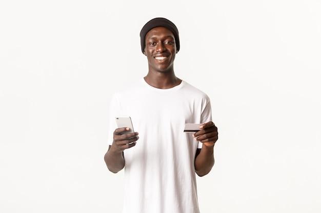 Portret szczęśliwego i zadowolonego, przystojnego afroamerykanina używającego karty kredytowej i telefonu komórkowego do robienia zakupów online lub logowania się na konto bankowości elektronicznej