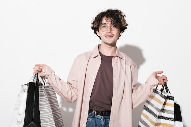 Portret szczęśliwego kupującego z torbami na zakupy uśmiechający się do kamery na białym tle