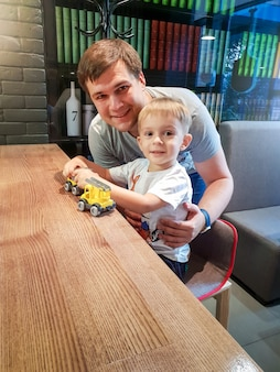 Portret szczęśliwego małego chłopca bawiącego się z ojcem plastikowymi zabawkami, siedząc za biurkiem w kawiarni