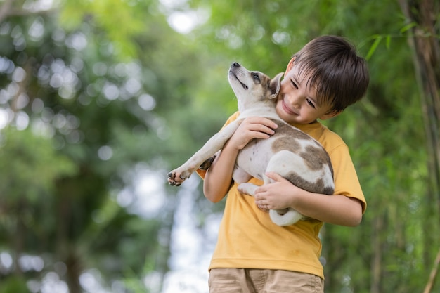Portret szczęśliwego małego chłopca bawiącego się ze swoim uroczym szczeniakiem