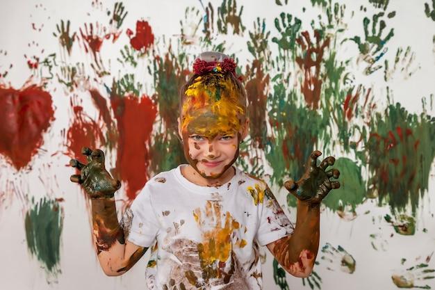 Portret szczęśliwego małego dziecka bawi się akwarelą. twarz dziecka i ubrania losowo pomalowane farbami. koncepcja zabawy dla dzieci, gry plastyczne i chuligaństwo. kolorowy obraz na festiwal holi. skopiuj miejsce