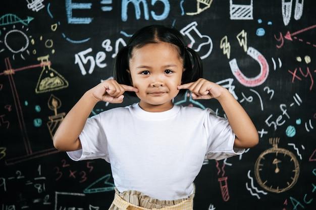 Portret szczęśliwego małego ucznia stojącego przed tablicą edukacyjną z uroczą postawą