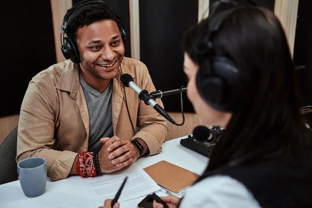 Portret szczęśliwego męskiego prezentera radiowego uśmiechającego się rozmawiającego z gościem podczas moderowania programu na żywo
