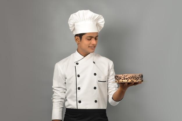 Portret szczęśliwego męskiego szefa kuchni ubranego w mundur trzymający talerz z czekoladowym ciastem patrzącego na ciasto