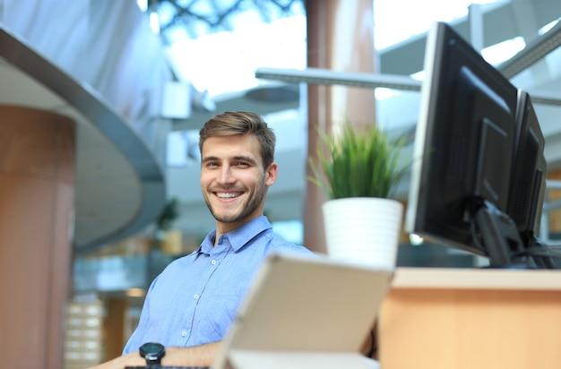 Portret szczęśliwego mężczyzny siedzącego przy biurku, patrzącego na kamerę, uśmiechającego się