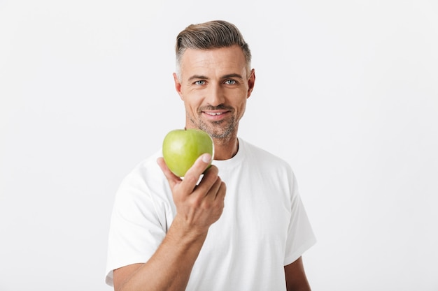 Portret szczęśliwego mężczyzny z lat 30. z włosiem pozuje i trzyma w ręku zielone jabłko na białym tle