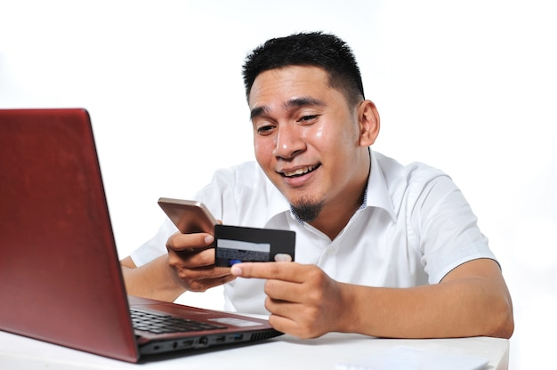 Portret szczęśliwego młodego azjatyckiego mężczyzny korzystającego z karty kredytowej/debetowej, na białym tle