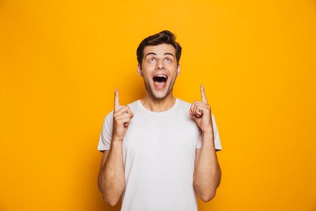 Portret szczęśliwego młodego człowieka, wskazując palcami w górę