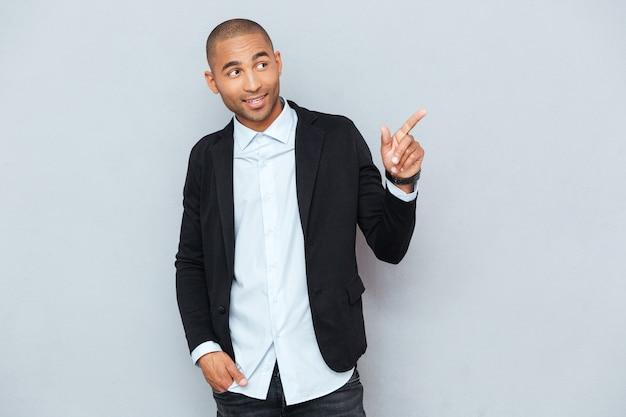 Portret szczęśliwego młodego człowieka wskazującego na coś interesującego na białym tle