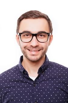 Portret szczęśliwego młodego inteligentnego mężczyzny w okularach na białej ścianie