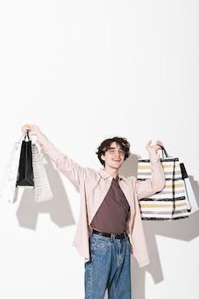 Portret szczęśliwego młodego klienta zadowolonego ze swoich zakupów stojącego na białym tle