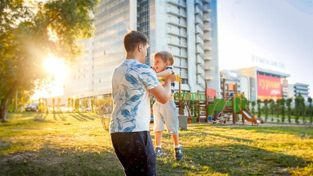 Portret szczęśliwego młodego ojca przytulającego i kręcącego swojego uśmiechniętego małego synka w parku