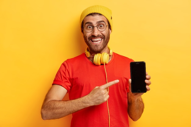 Portret szczęśliwego nieogolonego faceta wskazuje na ekran smartfona, demonstruje wyświetlacz, cieszy się z zakupu nowego urządzenia elektronicznego, nosi stylowy kapelusz i swobodną czerwoną koszulkę, modele na żółtej ścianie