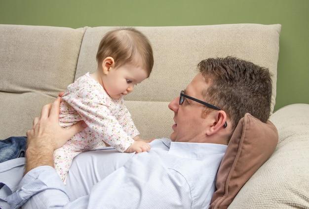 Portret szczęśliwego ojca bawiącego się słodkim dzieckiem siedzącym nad brzuchem na kanapie w domu