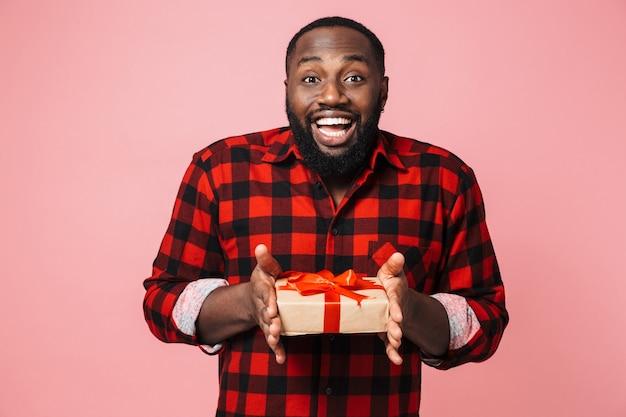 Portret szczęśliwego podekscytowanego afrykańskiego mężczyzny noszącego koszulę stojącego na białym tle, pokazującego obecne pudełko