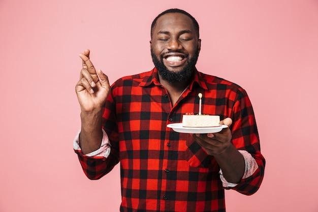 Portret szczęśliwego podekscytowanego afrykańskiego mężczyzny noszącego koszulę stojącego na białym tle, trzymającego talerz z tortem urodzinowym, trzymającego skrzyżowane palce