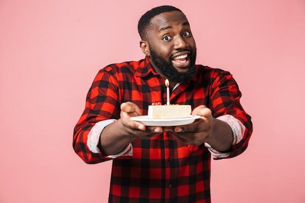 Portret szczęśliwego podekscytowanego afrykańskiego mężczyzny noszącego koszulę stojącego na białym tle, trzymającego talerz z tortem urodzinowym