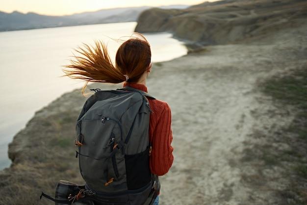 Portret szczęśliwego podróżnika w górach na zewnątrz w pobliżu morskiego krajobrazu zabawy