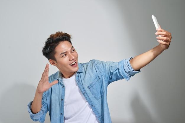 Portret szczęśliwego przypadkowego mężczyzny, który robi zdjęcie selfie na smartfonie na białym tle
