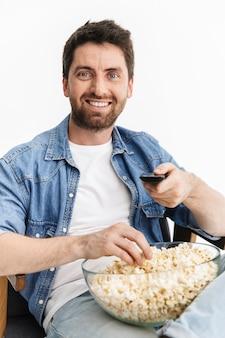 Portret szczęśliwego przystojnego brodatego mężczyzny noszącego zwykłe ubrania, siedzącego na krześle na białym tle, oglądającego film, jedzącego popcorn