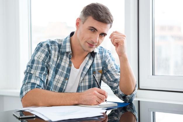 Portret szczęśliwego przystojnego mężczyzny siedzącego przy stole i piszącego
