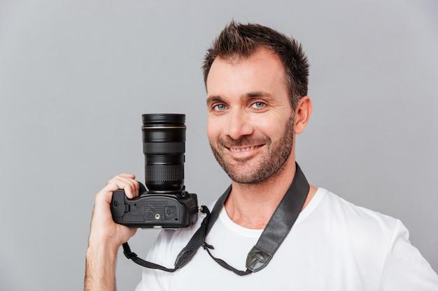 Portret szczęśliwego przystojnego mężczyzny trzymającego aparat na białym tle na szarym tle