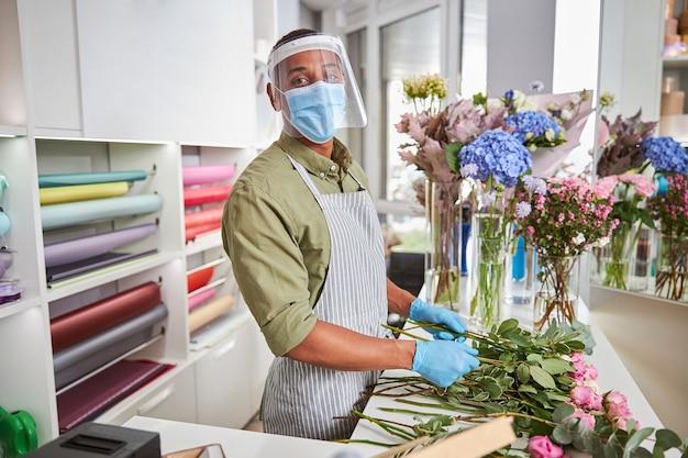 Portret szczęśliwego przystojnego mężczyzny w masce i szkle robi bukiety róż w sklepie podczas pandemii