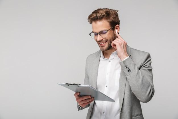 Portret szczęśliwego przystojnego mężczyzny w okularach za pomocą słuchawek i trzymającego schowek na białym tle nad białą ścianą