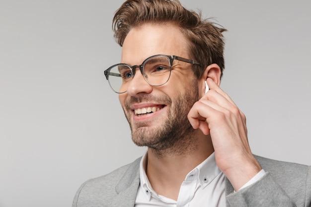 Portret szczęśliwego przystojnego mężczyzny w okularach za pomocą słuchawek i uśmiechnięty na białym tle nad białą ścianą