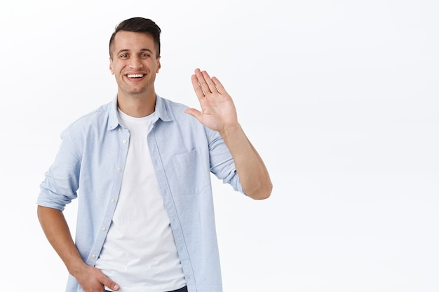 Portret szczęśliwego przystojnego młodzieńca mówiącego cześć, machającego podniesioną ręką nieformalnego powitania, miło cię poznać lub znak powitania, uśmiechnięty zadowolony, poznawanie nowych ludzi dołączonych do firmy, biała ściana