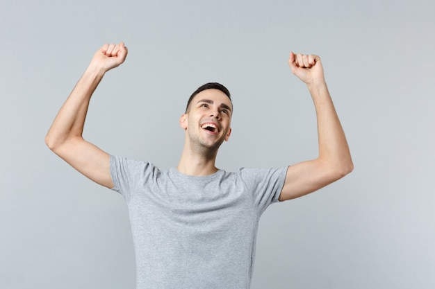 Portret szczęśliwego, radosnego młodego mężczyzny w zwykłych ubraniach, patrzącego w górę, wznoszących się rąk, zaciskających pięści jak zwycięzca