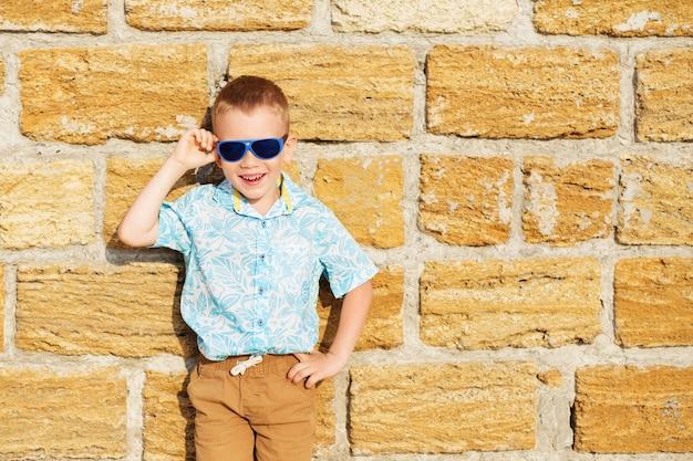 Portret szczęśliwego radosnego pięknego małego chłopca noszącego niebieskie lustrzane okulary przeciwsłoneczne