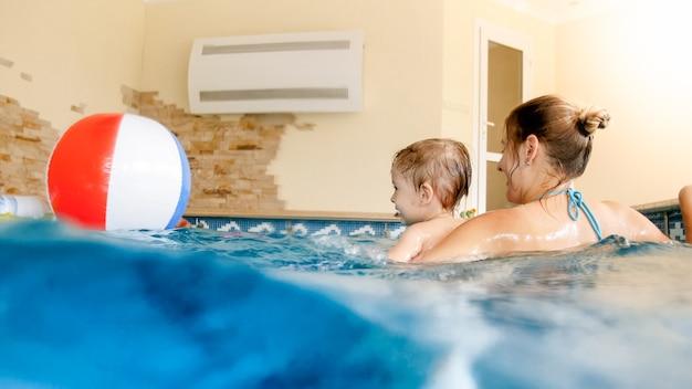 Portret szczęśliwego roześmianego chłopca z młodą matką bawi się kolorową nadmuchiwaną piłką plażową w basenie w letnim kurorcie