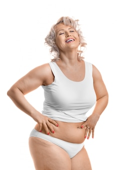 Portret szczęśliwego roześmianego modelu w średnim wieku plus size w białej bieliźnie.